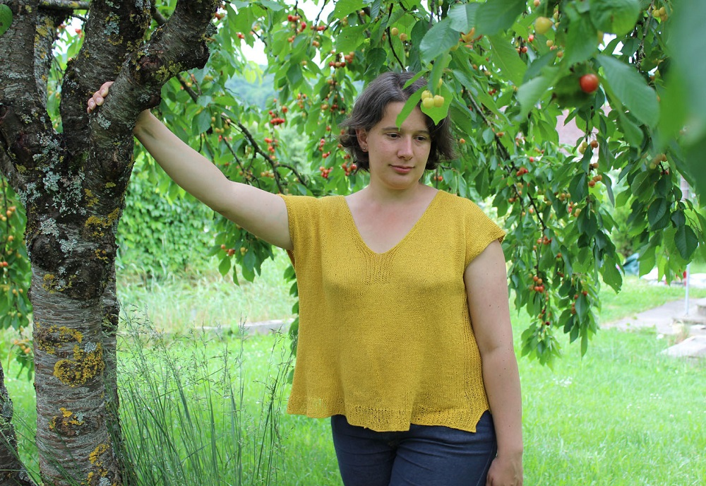 woman wears a yellow summery linen top with V-neck and drop shoulders under a tree full of cherries