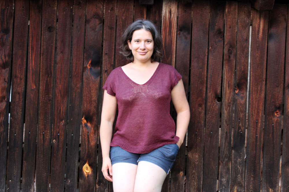 Woman wearing a burgundy linen top in front of a dark wooden fence.