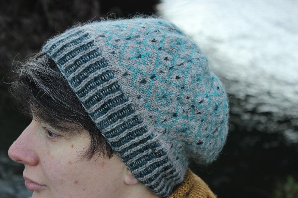 Vue de profil d'un bonnet en jacquard à 3 couleurs, avec la bordure en brioche bicolore