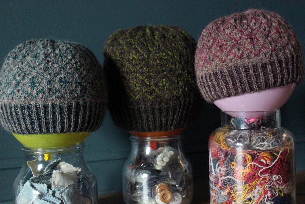 3 stranded-colourwork hat are drying on 3 balloons, put above glass jar (filled with yarn scraps and buttons)